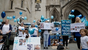 Supporters of critically ill baby Charlie Gard shout and hold placards before his parents Connie Yates and Chris Gard arrived at the High Court in London, Monday, July 24, 2017. (AP / Matt Dunham)