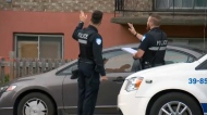 Police stand outside an apartment building where witnesses say a pregnant woman was stabbed multiple times with a BBQ fork on July 24, 2017