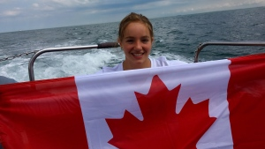 Emily Epp is seen in an undated handout photo holding Canadian flag on board a boat on the English Channel. (THE CANADIAN PRESS/HO-Epp Family)