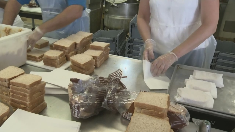 Volunteers make lunches for children at summer camp