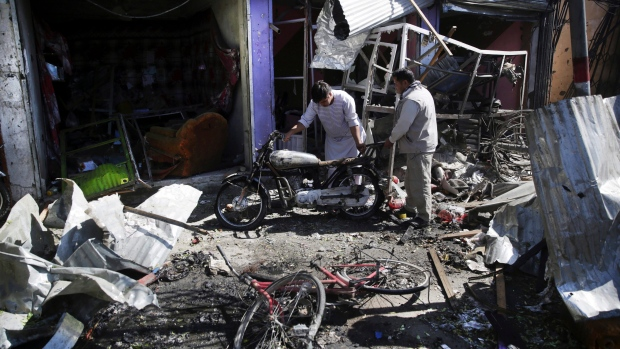 Men look at the remains of their properties at the site of a suicide attack in Kabul, Afghanistan, Monday, July 24, 2017. (Massoud Hossaini/AP Photo)