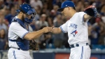 Toronto Blue Jays pitcher Roberto Osuna and catcher Martin Russell celebrate defeating the Oakland Athletics in AL baseball action in Toronto, Monday, July 24, 2017. THE CANADIAN PRESS/Fred Thornhill
