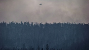 A helicopter is used to battle a wildfire burning on the top of a mountain near Ashcroft, B.C., on July 10, 2017. (Darryl Dyck / THE CANADIAN PRESS)