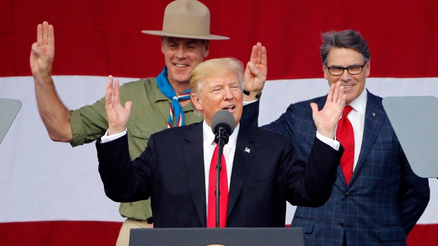 U.S. President Donald Trump, front left, gestures as former boys scouts, Interior Secretary Ryan Zinke, left, Energy Secretary Rick Perry, watch at the 2017 National Boy Scout Jamboree at the Summit in Glen Jean,W. Va., Monday, July 24, 2017. (AP Photo/Steve Helber)