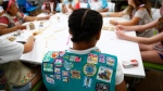 In this July 21, 2017 photo, badges are seen on the vest of a member of the Girl Scouts of Central Maryland as Girl Scouts participate in an activity introducing them to the world of robotics in Owings Mills, Md. (AP Photo/Patrick Semansky)
