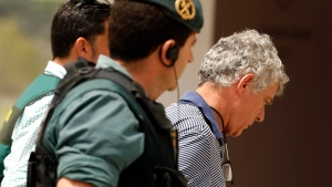 FILE - A Tuesday, July 18, 2017 file photo showing former President of the Spanish Football Federation, Angel Maria Villar, right, as he is lead by Spanish Civil Guard policeman to enter the Federation headquarters during an anti-corruption operation in Las Rozas, outside Madrid. (AP Photo/Francisco Seco, File)