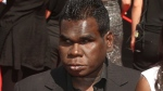 In this Nov. 27, 2011, file photo, aboriginal singer Geoffrey Gurrumul Yunupingu, left, arrives for the Australian Record Industry Association awards in Sydney, Australia. Yunupingu, renowned for singing in his native Yolngu language with a heart-rending voice and a unique guitar-playing style has died, his recording label said Wednesday, July 26, 2017. He was 46. (AP Photo/Rob Griffith, File)
