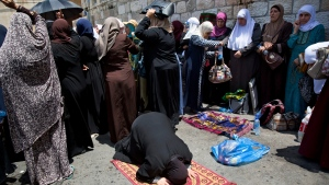 Palestinians women pray at the Lion's Gate following an appeal from clerics to pray in the streets instead of inside the Al Aqsa Mosque compound, in Jerusalem's Old City, Tuesday, July 25, 2017. (AP Photo/Oded Balilty)