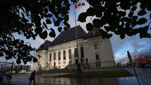 A pedestrian walks past the Supreme Court of Canada in Ottawa, Oct. 18, 2013. (Sean Kilpatrick / THE CANADIAN PRESS/