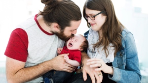 Baby Sebastian Havill, who successfully received a surgical procedure on his heart while he was in his mother's womb, is shown with his parents Kristine Barry, right, and Christopher Havill, left, at The Hospital for Sick Children in Toronto on Tuesday, July 25, 2017. (THE CANADIAN PRESS/Michelle Siu)