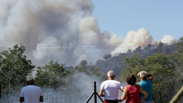 People watch smoke rising above a forest as a wildfire burns near La Londe-les-Maures on the French Riviera, Wednesday, July 26, 2017. (Claude Paris / AP)