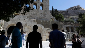 In this Thursday, July 6, 2017 file photo tourists take photographs the Herod Atticus theatre and Parthenon temple atop of Acropolis hill during a three-hour work stoppage in Athens. (AP Photo/Thanassis Stavrakis, File)
