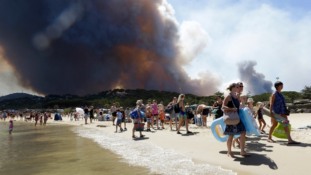 Sunbathers being evacuated from the beach in Le Lavandou, French Riviera, as plumes of smoke rise in the air from burning wildfires, Wednesday, July 26, 2017. (AP / Claude Paris)