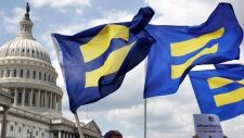 People with the Human Rights Campaign hold up 'equality flags' during an event organized by Rep. Joe Kennedy, D-Mass., in support of transgender members of the military, Wednesday, July 26, 2017, on Capitol Hill in Washington. (AP Photo / Jacquelyn Martin)