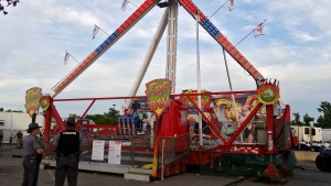 Authorities stand near the Fire Ball amusement ride after the ride malfunctioned injuring several at the Ohio State Fair, Wednesday, July 26, 2017, in Columbus, Ohio. Some of the victims were thrown from the ride when it malfunctioned Wednesday night, said Columbus Battalion Chief Steve Martin. (Jim Woods / The Columbus Dispatch via AP)