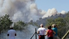 People watch smoke rising above a forest as a wildfire burns near La Londe-les-Maures on the French Riviera, Wednesday, July 26, 2017. Authorities ordered the evacuation of 10,000 people as fires hopscotched around the Riviera for a third day Wednesday, tearing through the forest of La Londe-les-Maures. (AP Photo/Claude Paris)