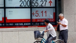 A man on bicycle looks at an electronic stock board showing Japan's Nikkei 225 index at a securities firm in Tokyo Thursday, July 27, 2017. (AP Photo/Eugene Hoshiko)