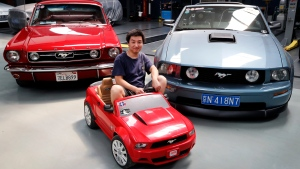 In this Wednesday, June 28, 2017, photo, Guo Xin sits on a toy Mustang as he poses with his 1966 MT GT Fastback, left, and 2005 GT convertible at his garage in Beijing. (Andy Wong/AP)