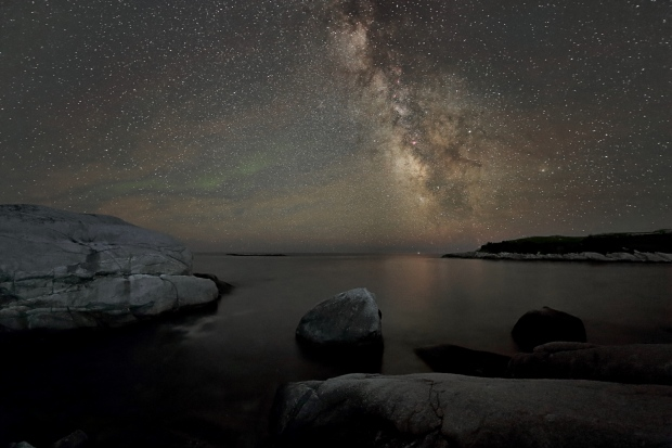 This amazing photo was taken by Barry Burgess, last night at Polly Cove NS.  The Milky Way is obvious, but what is the green light in the sky?