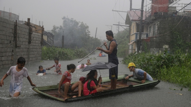 "Boys play outside their flooded homes after heavy rains from tropical storm ""Nesat"" flooded parts of metropolitan Manila, Philippines on Thursday, July 27, 2017. (AP Photo/Aaron Favila)"
