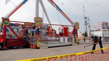 An Ohio State Highway Patrol trooper removes a ground spike from in front of the fire ball ride at the Ohio State Fair, Thursday, July 27, 2017, in Columbus, Ohio. (AP / Jay LaPrete)