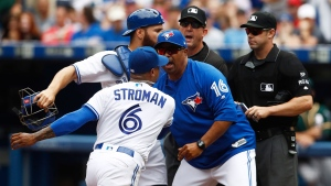 Toronto Blue Jays bench coach DeMarlo Hale, tries to hold back Blue Jays starting pitcher Marcus Stroman (6) and catcher Russell Martin (55) after they were ejected by umpire Will Little, right, during fifth inning American League MLB baseball action against the Oakland Athletics in Toronto on Thursday, July 27, 2017. THE CANADIAN PRESS/Mark Blinch