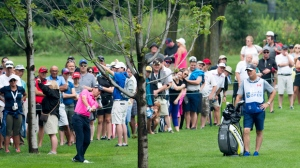 Mike Weir hits out from behind a tree on the 1st hole during the first round of the Canadian Open golf tournament at Glen Abbey in Oakville, Ontario on Thursday July 27, 2017. THE CANADIAN PRESS/Frank Gunn
