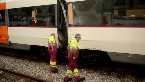 Workers look at a damaged train on the platform of a train station in Barcelona, Spain, Friday, July 28, 2017. Catalan government officials say dozens of people were treated for injuries when a morning commuter train they were traveling on crashed into the buffers in a station in northeastern Barcelona early Friday. (AP Photo/Adrian Quiroga)