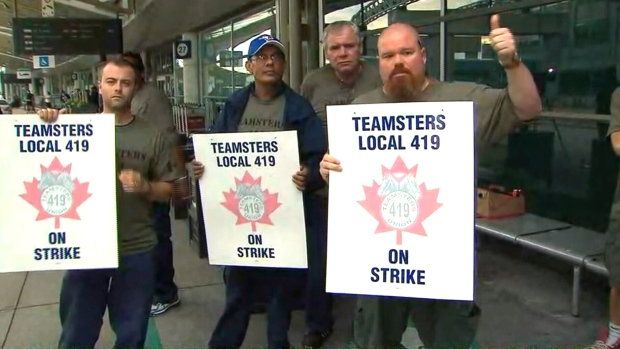 Striking ground crew workers hold picket signs at Pearson airport in Toronto, Friday, July, 28, 2017.