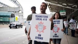 Striking workers are seen picketing at Pearson International Airport in Toronto on Friday, July, 28, 2017. THE CANADIAN PRESS/Christopher Katsarov