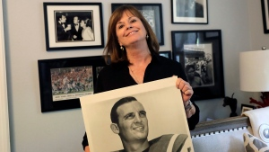 Lise Hudson poses with photos of her husband, Jim Hudson, who played football for the University of Texas and the New York Jets in the 1960's, at her home in Austin, Texas on July 25, 2017. (AP Photo/Eric Gay)