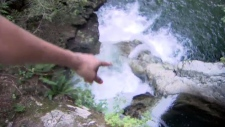 A person points to a popular swimming spot at Twin Falls, in Lynn Canyon Park, in North Vancouver, B.C.
