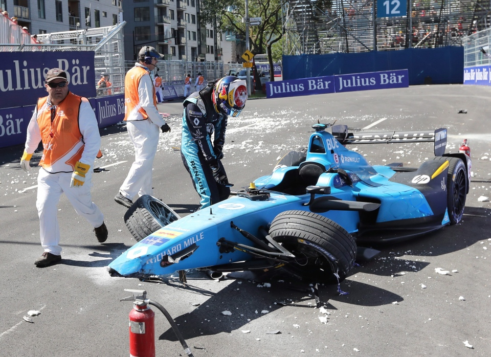 Sebastien Buemi, of Switzerland, checks the damage to his car after crashing during the second practice session at the Montreal Formula ePrix electric car race, in Montreal. (Ryan Remiorz/ The Canadian Press)