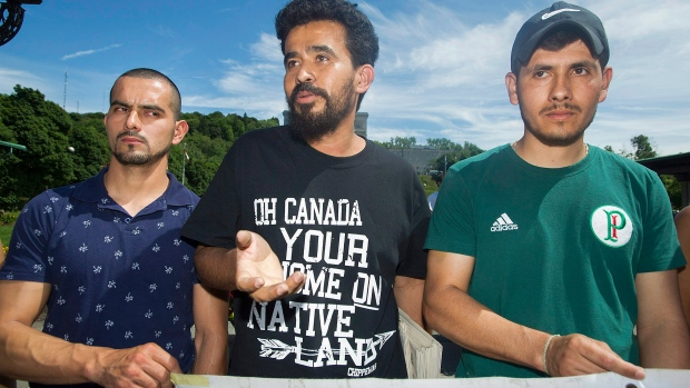 Migrant workers, from left, Erick Lopez, Noe Arteaga and Henry Aguirre from Guatemala speak during a demonstration in Montreal, Sunday, July 23, 2017. (THE CANADIAN PRESS/Graham Hughes)