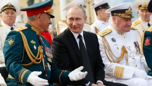 Russian President Vladimir Putin, centre, smiles chatting with Defence Minister Sergei Shoigu as they attend the military parade during the Navy Day celebration in St.Petersburg, Russia, on Sunday, July 30, 2017. (AP Photo/Alexander Zemlianichenko, Pool)