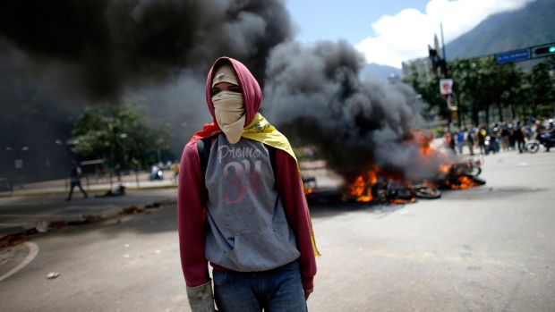 A demonstrators walks near a pile of privately owned motorcycles burned by the police after an explosion at Altamira square during clashes with anti-government demonstrators in Caracas, Venezuela, Sunday, July 30, 2017. The explosion injured several officers and damaged several of their motorcycles. The officers were then seen throwing several privately owned motorcycles into the remaining fire in reprisal. (AP Photo / Ariana Cubillos)