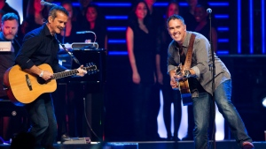 "Astronaut Chris Hadfield plays with Barenaked Laides singer Ed Robertson, right, during ""We Day"" in Toronto, September 20, 2013. (Mark Blinch/THE CANADIAN PRESS)"