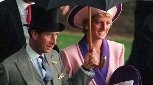 In this Wednesday, June 20, 1990 file photo, Diana and Prince Charles, take shelter under an umbrella while attending the second day of the Royal Ascot horse race meet near London. (AP Photo/Martyn Hayhow, File)