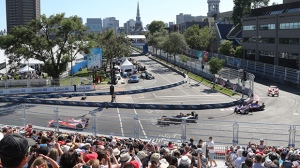 Drivers pass through the first turn at the Montreal Formula ePrix electric car race, in Montreal on Sunday, July 30, 2017. THE CANADIAN PRESS/Tyler Remiorz