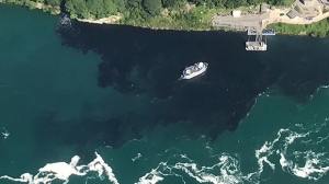 In this July 29, 2017 photo provided by Rainbow Air INC., black-colored wastewater treatment discharge is released into water below Niagara Falls, in Niagara Falls, N.Y. (Patrick J. Proctor/Rainbow Air INC. via AP)