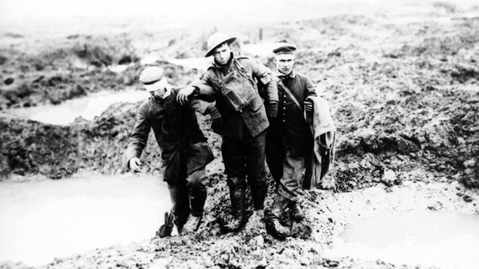 FILE - In this 1917 photo, wounded Canadian and German First World War soldiers help one another through the mud during the Battle of Passchendaele, in Passchendaele, Belgium. (AP Photo/FILE)