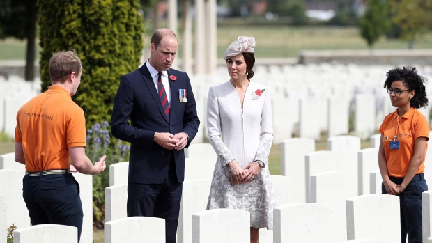 Britain's Prince William and Kate Duchess of Cambridge meet interns for the Commonwealth War Graves Commission Angus Urquhart, left and Alisha Saleh as they visit Bedford House Cemetery on the outskirts of Ypres, Belgium Monday July 31, 2017. Ceremonies are taking in place in Ypres to commemorate the centenary of the Battle of Passchendaele. (Andrew Matthews/PA via AP)
