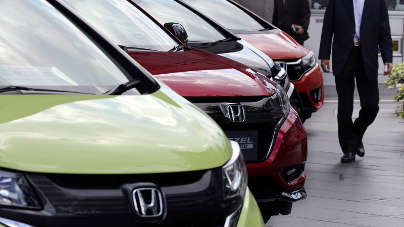 A man walks past Honda cars on display at Honda Motor Co. headquarters in Tokyo on April 28, 2017. (Koji Sasahara/AP)