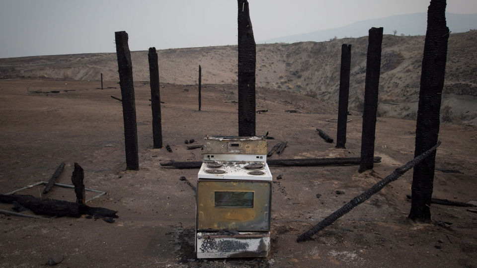 A stove sits among the remains of a structure that burned in a wildfire on the Ashcroft First Nation near Ashcroft, B.C., on Tuesday August 1, 2017. (THE CANADIAN PRESS/Darryl Dyck)