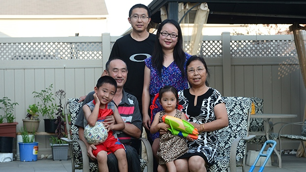 Yi Jiang and husband Jianqiao Sun, back, stand as grandparents Youfang Jiang and Li Zhang sit with grandson Sunny Jiang and granddaughter Jenny Sun in the backyard of their home in Ottawa on Monday, July 31, 2017. THE CANADIAN PRESS/Sean Kilpatrick