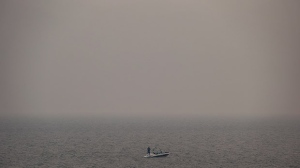 Thick smoke from wildfires fills the air as a man stands on a boat while fishing on Kamloops Lake west of Kamloops, B.C., on Tuesday, Aug. 1, 2017. (Darryl Dyck / THE CANADIAN PRESS)