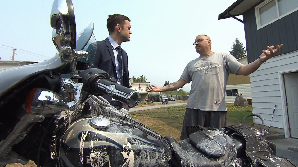 Rob Supeene, right, speaks to CTV News' David Molko after his Harley-David motorcycle was vandalized in Coquitlam.
