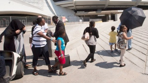 A group of asylum seekers leave Olympic Stadium to go for a walk, in Montreal on Wednesday, August 2, 2017. (Ryan Remiorz / THE CANADIAN PRESS)