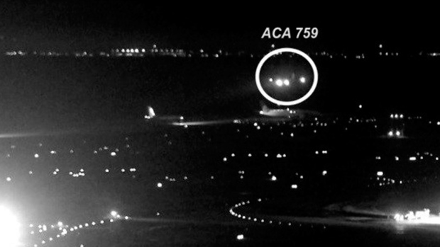 This image taken from San Francisco International Airport video and annotated by source, shows the Air Canada plane flying just above a United Airlines flight waiting on the taxiway. (NTSB via AP)