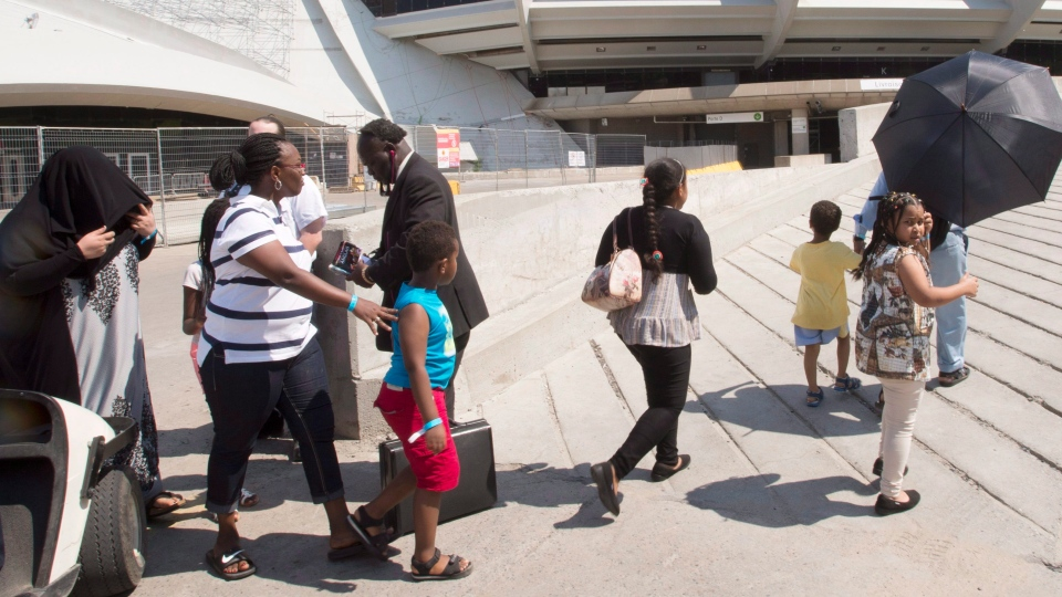 A group of asylum seekers leave Olympic Stadium to go for a walk, in Montreal on Wednesday, August 2, 2017. The stadium is being used as temporary housing to deal with the influx of asylum seekers arriving from the United States. (THE CANADIAN PRESS/Ryan Remiorz)